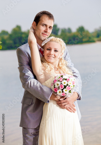 handsome tall groom hugging blonde bride from back against river
