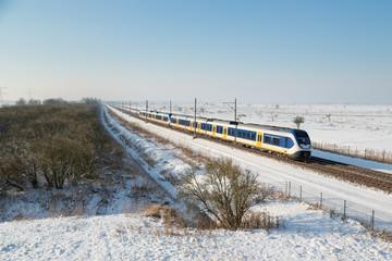 Yellow train in Dutch rural winter landscape