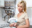 housewife counts up money for repair of gas water heater
