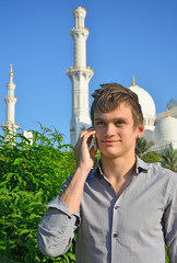 Smiling young man with a cell phone in front of mosque