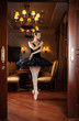 Ballerina in black tutu standing on pointes in luxury interior
