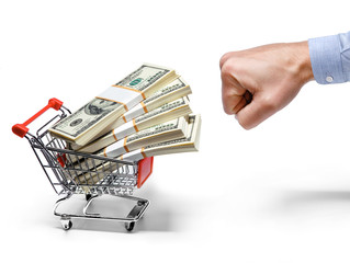 fist and shopping cart full of stacks of dollar bills