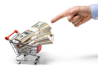 finger and shopping cart full of stacks of dollar bills