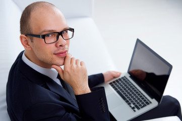 Smiling businessman sitting with laptop