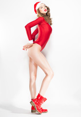 sexy woman in red christmas costume with red glossy boots posing