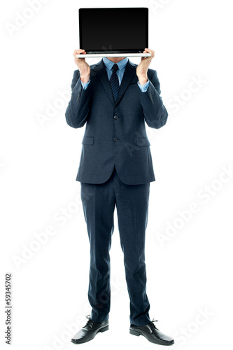 Businessman covering his face with laptop