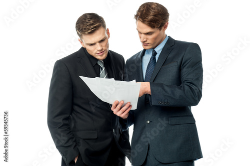 Businessmen evaluating deal documents