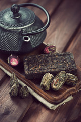 Variety of dry tea and cast-iron teapot, wooden background