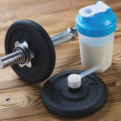 Dumbbell, protein shake and a measuring scoop with protein