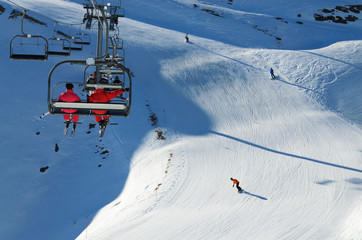 Skiers in a chair lift above the downhills
