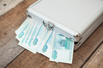 Closed steel case with Russian banknotes inside on wooden floor