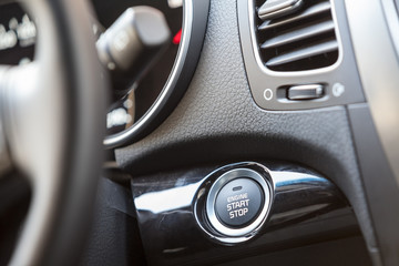 Car interior, engine start button under steering wheel