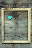 Vintage wooden frame with heart on a grunge background
