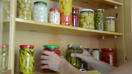 hand take from shelves cupboard different size jars vegetables