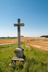altes Kreuz vor abgeernteten Feldern