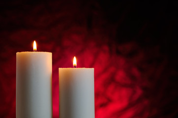 two candles with red background