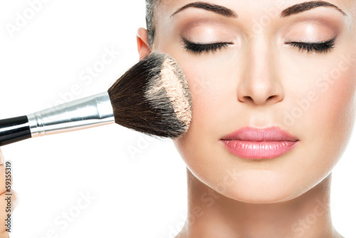 woman  applying dry cosmetic tonal foundation  on the face - 59355319