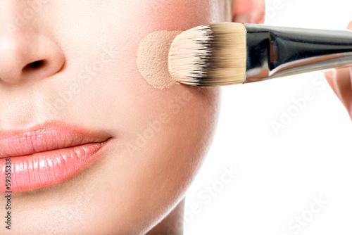 Poster Makeup artist applying liquid tonal foundation  on the face