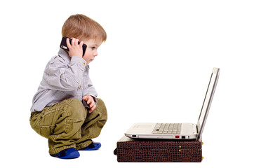 Beautiful boy speaks on the phone looking at laptop