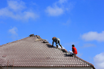 Workers   repair  concrete  roof  tile