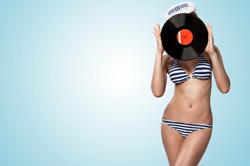 A photo of pin-up girl in bikini holding a Vinyl LP over face.