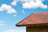 Edge of the roof of a wooden house on a background of blue sky