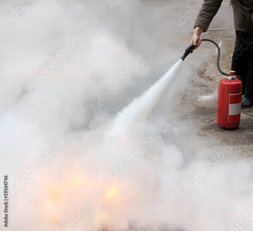 Fire fighting woman demonstrating how to use a fire extinguisher