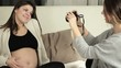 Young woman uses camera to take a picture of her pregnant friend