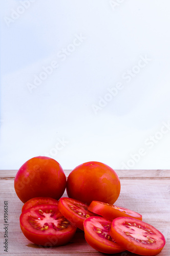 chopped and whole tomatoes on chopping board