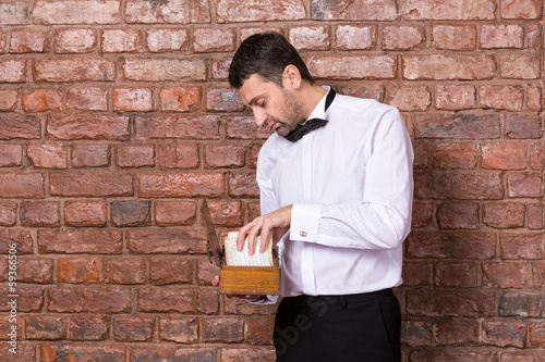 Man reading a document from a wooden box