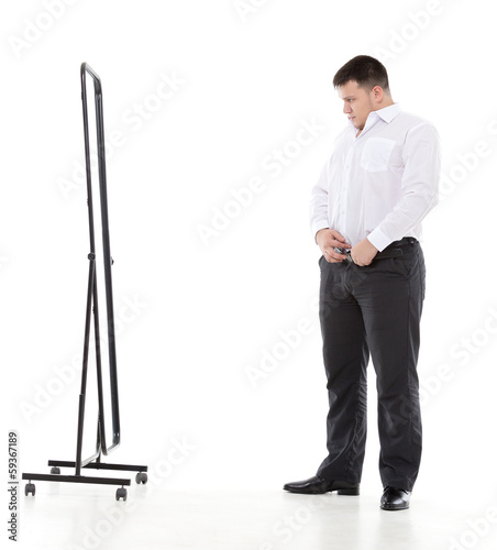 Overweight man admiring himself in a mirror