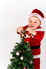 Baby boy dressed as Santa Claus putting the star on the top of C
