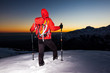 Winter hiking: man stands on a snowy ridge looking at the sunset