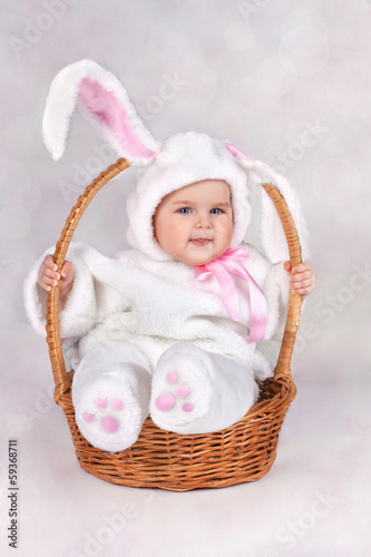 child dressed as a bunny in a basket