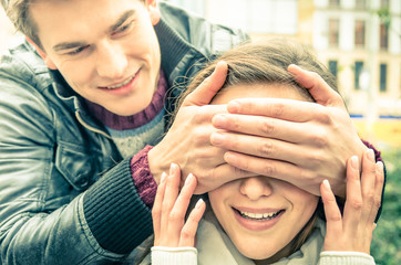 Young man covering the eyes of an happy surprised girlfriend