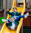 two children  on slide at playground