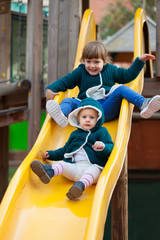 two happy children  on slide at playground