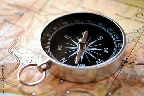 Leinwandbild Motiv Handheld compass on a map