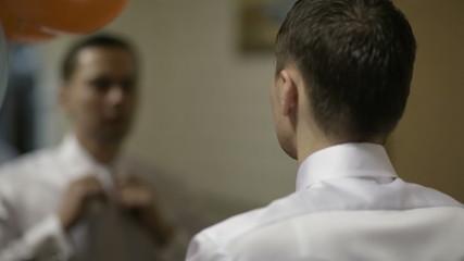 Groom fixing his tie.
