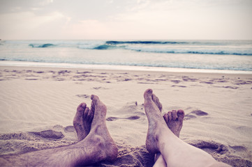Woman and man (legs and foot) in the beach, vintage style