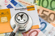 Leinwanddruck Bild - Stethoskop mit Gesundheitskarte auf Geldscheinen