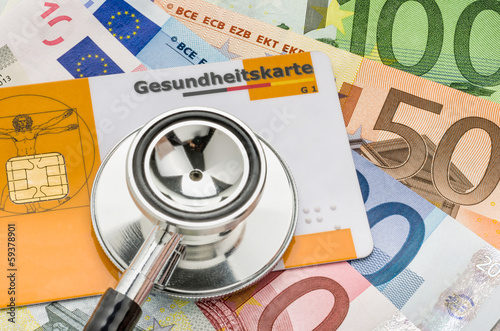 Leinwandbild Motiv Stethoskop mit Gesundheitskarte auf Geldscheinen