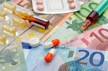 Spritze und Medikamente auf Geldscheinen