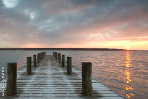 einsamer Holzsteg zum Sonnenaufgang