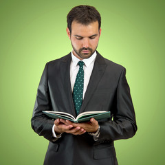 Business man reading a book over isolated background