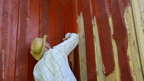 Worker man with glasses paint wood wall with brush in red color