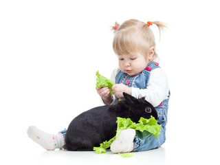 kid feeding a rabbit with lettuce