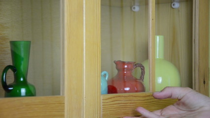 hand put green glass vase on the shelf next other vase