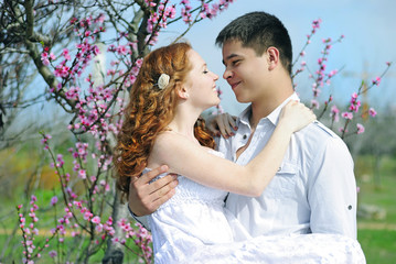 beautiful young couple in love among the flowering trees