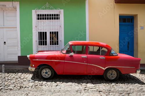 Roter Oldtimer vor bunten Häusern, Kuba - 59383378